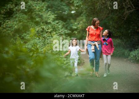 Mère et filles marchant sur le chemin dans les bois