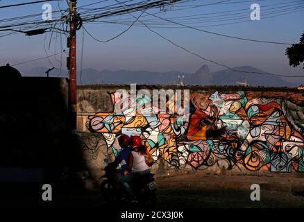 Les gens qui voyagent sur une moto passent par un graffiti face à la baie de Guanabara à Rio de Janeiro, le 27 février 2015. Rio de Janeiro marque le 450e anniversaire de sa fondation le 1er mars. Photo prise le 27 février 2015. REUTERS/Pilar Olivares (BRÉSIL - Tags: ANNIVERSAIRE DE LA SOCIÉTÉ POLITIQUE)