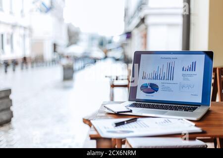 gros plan. ordinateur portable et tableau financier sur une table dans un café de rue.