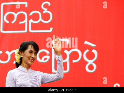 Myanmar pro-democracy leader Aung San Suu Kyi waves toward her supporters after finishing her address during the election campaign at Mon State in Myanmar March 11, 2012. REUTERS/Staff (MYANMAR - Tags: POLITICS)