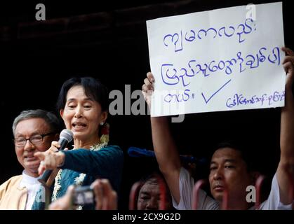 Aung San Suu Kyi addresses supporters outside her National League for Democracy party headquarters in Yangon November 14, 2010. The pro-democracy leader called for freedom of speech in army-ruled Myanmar on Sunday and urged thousands of supporters to stand up for their rights and not lose heart, indicating she might pursue a political role. The banner reads: 'I love the public too'.  REUTERS/Soe Zeya Tun   (MYANMAR - Tags: POLITICS SOCIETY)