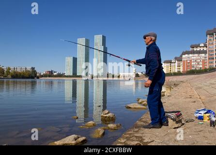 A man fishes on embankment of Ishim river in front of residential towers in Kazakhstan's capital Astana September 8, 2012.  REUTERS/Shamil Zhumatov  (KAZAKHSTAN - Tags: CITYSPACE SOCIETY) - Stock Photo