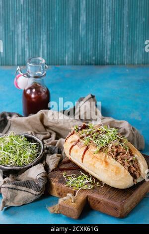 Sandwich de porc tiré avec de la viande, des pousses vertes et du ketchup barbecue, servi sur une planche à découper en bois avec une petite bouteille de sauce tomate et un bol de légumes verts