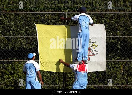 Players from a team of priests and seminarians hang a Vatican flag during a training session at the Maria Mater Ecclesiae's Catholic College in Rome October 22, 2013. The Vatican officially declared its intention to defeat the Church of England on Tuesday - not in a theological re-match nearly 500 years after they split, but on the cricket pitch. The challenge was launched at the baptism of the St. Peter's Cricket Club. Vatican officials said the league will be composed of teams of priests and seminarians from Catholic colleges and seminaries in Rome. REUTERS/Alessandro Bianchi (VATICAN - Tags