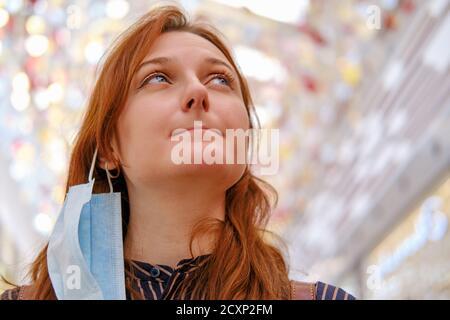 Une femme avec un masque enlevé après la fin de la quarantaine du coronavirus, un portrait en gros plan d'une fille à cheveux rouges. Copier l'espace pour le texte