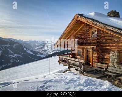 Ancienne ferme de cabane de montagne enneigée dans la région des pistes de ski De Saalbach Hinterglemm dans les alpes autrichiennes contre le ciel Banque D'Images