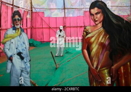 An employee of Anoop Touring Talkies, a travelling tent cinema company, stands between cut-outs of Bollywood actors Amitabh Bachchan and Rekha in Mumbai April 23, 2013. Indian cinema marks 100 years since Dhundiraj Govind Phalke's black-and-white silent film 'Raja Harishchandra' (King Harishchandra) held audiences spellbound at its first public screening on May 3, 1913, in Mumbai. Indian cinema, with its subset of Bollywood for Hindi-language films, is now a billion-dollar industry that makes more than a thousand films a year in several languages. It is worth 112.4 billion rupees (over $2 bill