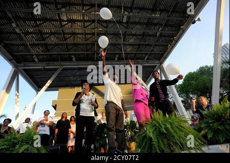 Les parents de Trayvon Martin, un adolescent de Floride tué, Tracy Martin (2e L) et Sybrina Fulton (2e R), Et le frère aîné de Trayvon, Javaris Fulton (R), est rejoint par la députée Frederica Wilson (D-FL) qui libère des ballons dans les airs à la mémoire de Trayvon vers la fin d'un rassemblement protestant contre son tir à Miami, en Floride, le 1er avril 2012. Dimanche, des milliers de manifestants se sont rassemblés dans un parc en bord de baie du centre-ville pour réclamer l'arrestation du volontaire de la montre du quartier qui a abattu un adolescent noir non armé, Trayvon Martin, dans le centre de la Floride, il y a un mois. REUTERS/Brian Blanco (ÉTATS-UNIS