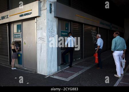 Les gens font la queue pour retirer de l'argent d'un guichet automatique (ATM) à l'extérieur d'une succursale de la Banque nationale à Athènes, Grèce le 17 juillet 2015. Un haut fonctionnaire grec a confirmé jeudi que les banques rouvriraient lundi et a déclaré que le gouvernement cherchait à permettre aux gens de procéder à des retraits de 60 euros sur plusieurs jours. REUTERS/Yiannis Kourtoglou