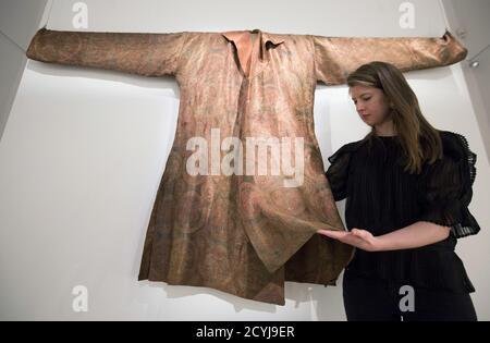 Un assistant de galerie pose avec une robe en soie du 7ème - 8ème siècle à un aperçu des arts de l'enchère mondiale islamique à Sotheby's à Londres le 17 avril 2015. On estime que le lot se vendra entre 225,000 $ et 300,000 $ (150,000-200,000 livres sterling) lorsqu'il est mis aux enchères le 21 avril à Londres. REUTERS/Neil Hall