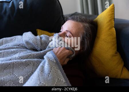 Femme âgée dormant sur un canapé à la maison
