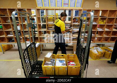 A postwoman of the German postal and logistics group Deutsche Post sorts mail at a sorting office in Berlin's Mitte district, December 4, 2013. Deutsche Post, the world's number one postal and logistics group, transported around 18 billion letters in 2012. REUTERS/Fabrizio Bensch (GERMANY  - Tags: BUSINESS EMPLOYMENT) - Stock Photo