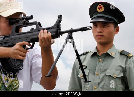 A visitor poses with a gun during an open day at the People's Liberation Army's (PLA) Ngong Shuen Chau Naval Base on Hong Kong's Stonecutters Island July 28, 2012. The naval base was open to the public on Saturday, four days ahead of the PLA Army Day on August 1. REUTERS/Tyrone Siu (CHINA - Tags: POLITICS MILITARY)