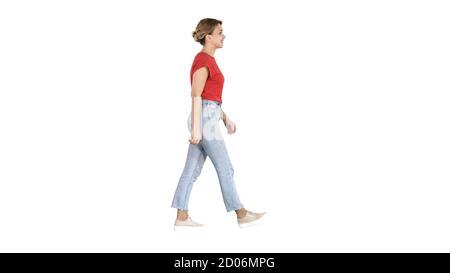Femme en t-shirt rouge, jeans et baskets marchant sur le dos blanc