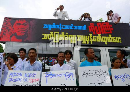 Ko Ko Gyi, a leader of the 88 Generation Students group, speaks as political activists hold placards during a demonstration for Ko Par Gyi in Yangon October 26, 2014. The protesters believe that Gyi, a freelance reporter, was killed after being detained by Myanmar's military as he was covering the front line of Kayin State on October 4. The banner reads, 'Need real investigation for the killing of freelance reporter Ko Par Gyi.' REUTERS/Soe Zeya Tun (MYANMAR - Tags: MEDIA CIVIL UNREST POLITICS)