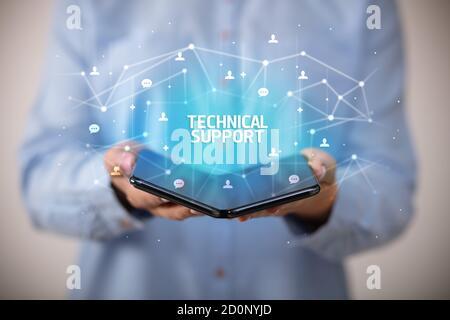 Businessman holding a smartphone pliable avec le soutien technique de l'inscription, la nouvelle technologie concept