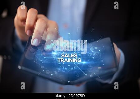 Businessman holding a smartphone pliable avec des ventes formations inscription, nouveau concept commercial