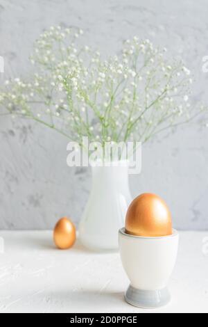 Gros plan de l'oeuf d'or dans la tasse d'oeuf sur le fond du bouquet de gypsophila. Joyeuses pâques