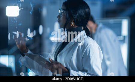 Dans le laboratoire de recherche Smart et belle Afro-américaine femelle Un scientifique portant un manteau blanc et des lunettes de protection écrit Formula on Verre