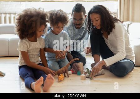 Heureux africain américain couple marié jouant des jouets avec de petits enfants. Banque D'Images