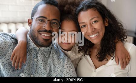 Souriant africain ethnicité petite fille enfant en cuddling mixte de race parents. Banque D'Images