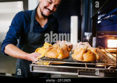Un homme mexicain qui cuit du pain appelé la poêle de muerto traditionnel de Le Mexique à Halloween