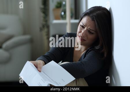 Triste femme se plaignant après avoir lu une lettre assise sur le étage seul à la maison dans la nuit