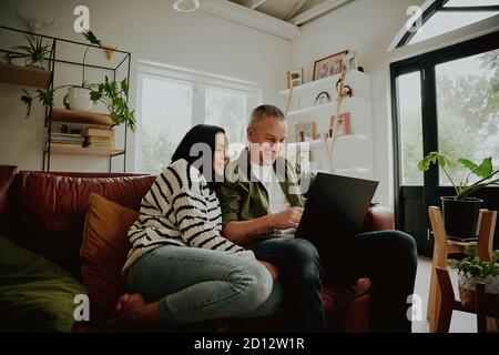 Jeune couple assis sur le canapé regardant un ordinateur portable - 2 personnes en streaming depuis leur ordinateur portable