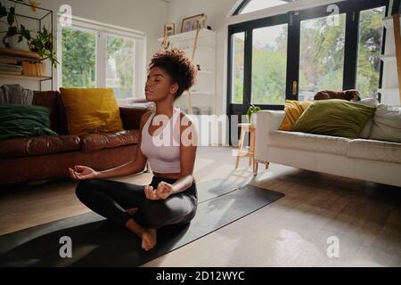 Jeune femme africaine méditant assise en position lotus à la maison sur le tapis de yoga
