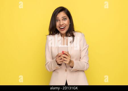 surprise jeune femme en costume rose tenant le téléphone et enthousiaste lire les nouvelles sur fond jaune