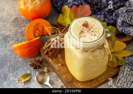 Latte épicée à la citrouille d'automne ou café en verre avec des ingrédients biologiques sur un comptoir en pierre légère.