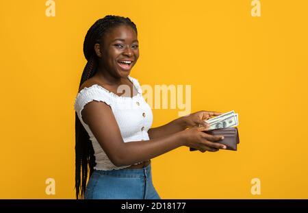 Finance, investissement et économies d'argent. Bonne femme noire mettant des billets dans un portefeuille