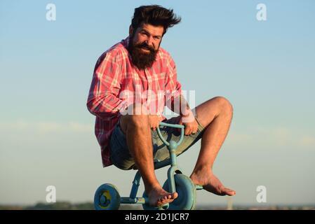Homme agissant comme un enfant. Drôle d'homme sur un vélo pour enfants. Vélo nerdy.