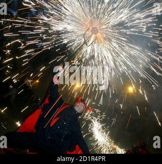 Un fêtard, habillé comme un démon, se passe dans les rues et joue avec des feux d'artifice dans le centre de Barcelone, Espagne, le 23 septembre 2005. Le feu d'artifice est une fête traditionnelle qui se produit chaque année en septembre en l'honneur du patron de Barcelone, saint la Merce. REUTERS/Albert Gea