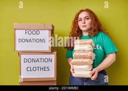 belle femme bénévole à tête rouge collectant un don pour pauvre, jeune fille avec des boîtes à carboboard sourires à la caméra, arrière-plan vert isolé