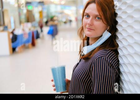 La femme a retiré le masque médical après la fin de la quarantaine du coronavirus. Portrait d'une fille aux cheveux rouges dans un centre commercial en gros plan