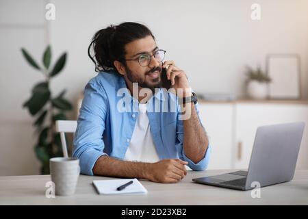 Homme indien du millénaire parlant sur le téléphone cellulaire et en utilisant l'ordinateur portable à Bureau à domicile