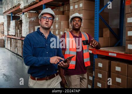 Homme d'affaires portant des lunettes tenant une tablette numérique tandis que l'employé de l'usine montre le superviseur autour de l'entrepôt.