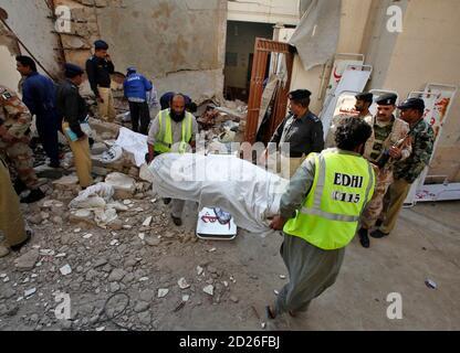 Les responsables de la sécurité font une enquête alors que les secouristes déplacent un corps mort dans une maison effondrée suite à une explosion à Karachi le 8 janvier 2010. Au moins six personnes ont été tuées dans la ville pakistanaise de Karachi vendredi, lorsque des explosifs stockés dans un refuge présumé pour militants ont apparemment été accidentellement renrrés, a déclaré la police. REUTERS/Akhtar Soomro (PAKISTAN - Tags: TROUBLES CIVILS CRIME DROIT POLITIQUE)