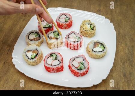 Divers sushis japonais sur plaque blanche avec baguettes sur bois arrière-plan