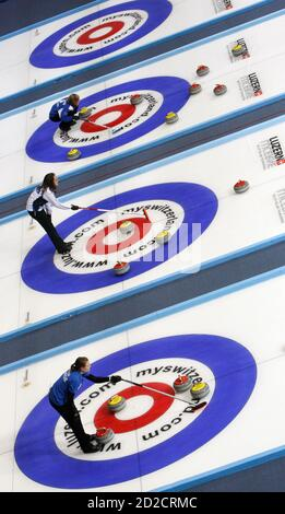 Curlers compete at the 2009 World Women's Curling Championship in Gangneung, east of Seoul March 21, 2009.  REUTERS/Lee Jae-Won (SOUTH KOREA SPORT CURLING IMAGE OF THE DAY TOP PICTURE) - Stock Photo