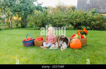 une petite fille est assise sur l'herbe parmi un variété de légumes Banque D'Images