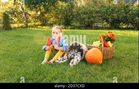 la fille est assise sur l'herbe parmi les légumes en tenant le poivre dans ses mains et en riant Banque D'Images