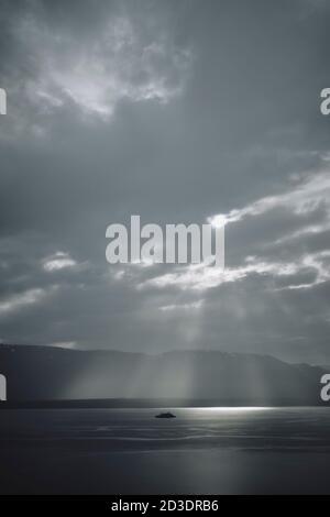 Un seul bateau de croisière dans un fjord et un ciel spectaculaires paysage avec puits de lumière du soleil qui brillent à travers les nuages Du nord de l'Islande