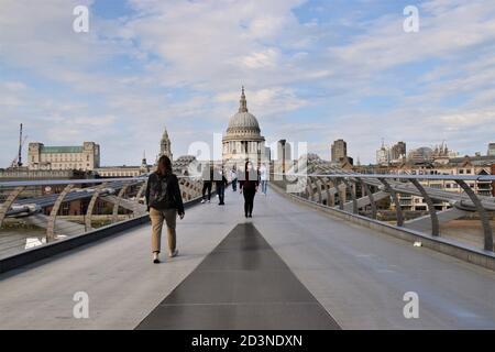 Une femme avec un masque facial protecteur traverse le pont du Millénaire avec la cathédrale St Paul en arrière-plan, Londres 2020