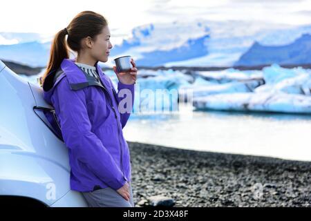 Camping camping-car. Femme buvant un café le matin devant le camping-car tout en conduisant une camionnette de camping sur la route de l'Islande. Chauffeur touristique asiatique