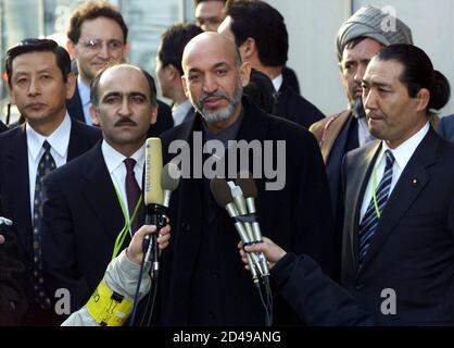Afghanistan's interim leader Hamid Karzai (C) is surrounded by security personnel on arrival at Tokyo's Haneda airport January 20, 2002. Karzai flew in to Japan to make his global debut at an international conference on the reconstruction of Afghanistan.