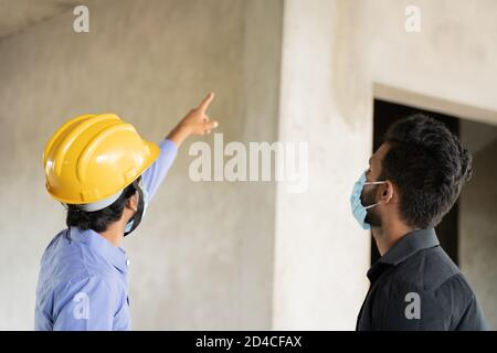Accent sélectif sur le hardhad, deux ouvriers de la construction dans le masque médical occupé dans le travail tout en maintenant la distanciation sociale - concept de covid-19 or