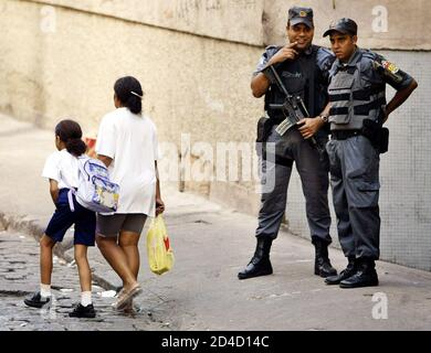 Une mère et sa fille marchent devant des policiers au bidonville de Pavao à Rio de Janeiro, le 27 février 2003. La police brésilienne a arrêté 20 personnes et en a tué deux autres lors d'une fusillade lorsqu'elle a balayé les bidonvilles de Rio pour contrer une vague de violence quelques jours avant le célèbre Carnaval de la ville. REUTERS/Sergio Moraes SM/HB