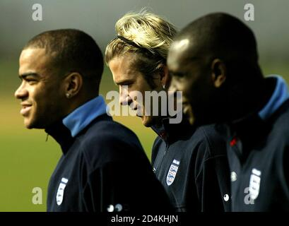 Le capitaine d'Angleterre et le milieu de terrain de Manchester United David Beckham (C), Kieron Dyer (L) de Newcastle United et l'attaquant de Liverpool Emile Heskey marchent sur le terrain lors d'une séance d'entraînement en Angleterre au camp d'entraînement d'Arsenal à Londres le 27 mars 2003. L'équipe se prépare pour les prochains matchs de qualification au championnat d'Europe contre le Liechtenstein à Vaduz le 29 mars et la Turquie à Sunderland le 2 avril. REUTERS/Kieran Doherty MD